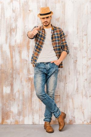 君に決めた!ハンサムな若い男見て、木製の壁に立っている間カメラを指しての全長 写真素材
