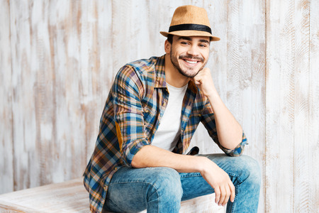 fedora hat: Casually handsome. Handsome young man wearing hat and looking at camera while sitting against the wooden wall