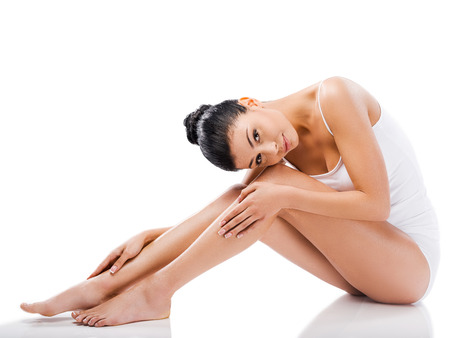 nude woman sitting: Slim beauty. Beautiful young woman looking at camera and holding hands on her legs while sitting against white background Stock Photo