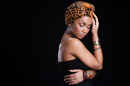 woman nude standing: True African beauty. Beautiful African woman wearing a headscarf and posing against black background