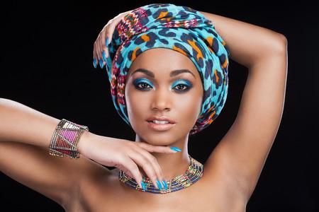 femme noire nue: Dans un style traditionnel africain. Belle femme africaine � foulard et des bijoux posant sur fond noir et regardant la cam�ra
