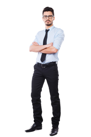 office attire: Confident businessman. Full length of handsome young man in shirt and tie keeping arms crossed and looking at camera while standing against white background