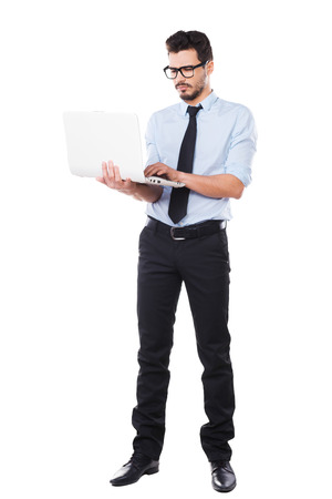 Supporting your business. Full length of handsome young man in shirt and tie working on laptop while standing against white background Stock Photo