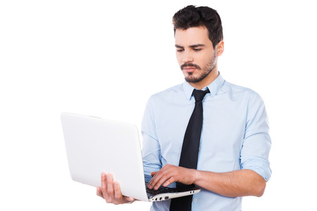 it background: Confident business expert. Handsome young man in shirt and tie working on laptop while standing against white background