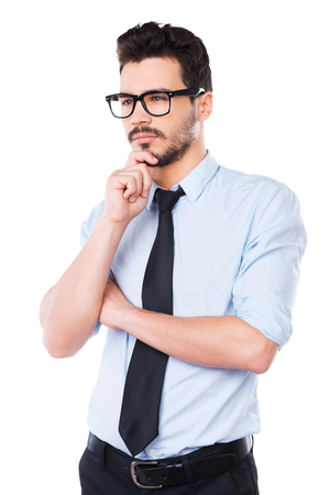 Waiting for inspiration. Thoughtful young man in shirt and tie looking away and touching his chin while standing against white background
