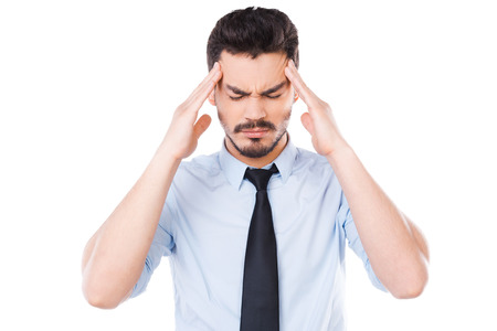 Too much stress. Frustrated young man in shirt and tie touching his head and keeping eyes closed while standing against white background photo