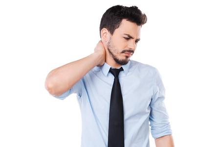 dolor: Sensación de dolor en el cuello. Hombre joven frustrado en camisa y corbata tocar su cuello y expresar negatividad mientras está de pie contra el fondo blanco