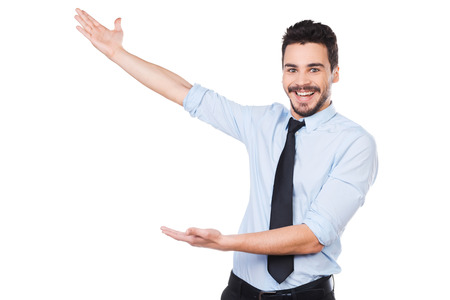 It is unbelievable! Happy young man in shirt and tie pointing away and smiling while standing against white background photo