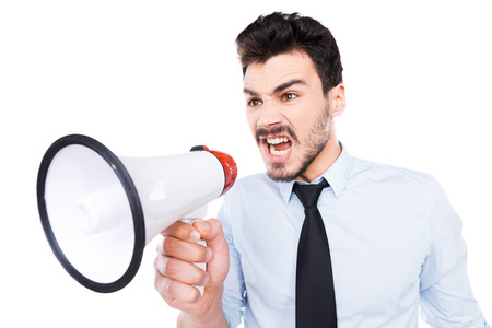 Listen to me! Furious young man in shirt and tie holding megaphone and shouting while standing against white background photo