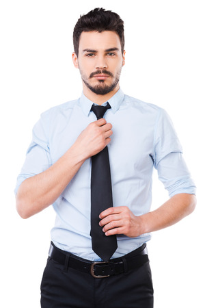 Everything should be perfect. Confident young man in shirt and tie looking at camera and adjusting his necktie while standing against white background