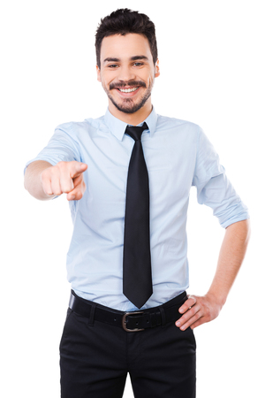 only one man: I choose you! Handsome young man in shirt and tie pointing you and smiling while standing against white background Stock Photo