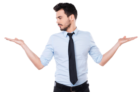 Making his choice. Handsome young man in shirt and tie making his choice while looking at one of his palms and standing against white background photo