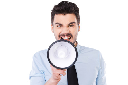businessman using a megaphone: Everybody listen to me! Furious young man in shirt and tie holding megaphone and shouting while standing against white background