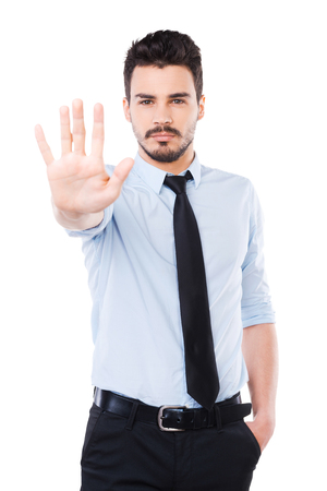 rejection: Stop it! Confident young man in shirt and tie showing his palm and looking at camera while standing against white background Stock Photo