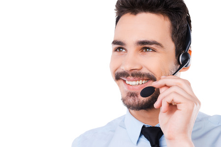 Always ready to help you. Portrait of handsome young male operator adjusting his headset and smiling while standing against white background Imagens