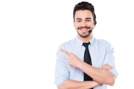 Advertising your product. Handsome young male operator pointing away and smiling while standing against white background