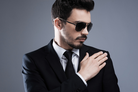 stubble: Used to perfection and success. Handsome young man in formalwear and sunglasses adjusting his jacket while standing against grey background