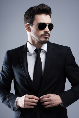 buttoning: Making business look good. Handsome young man in formalwear and sunglasses buttoning his jacket and looking away while standing against grey background Stock Photo