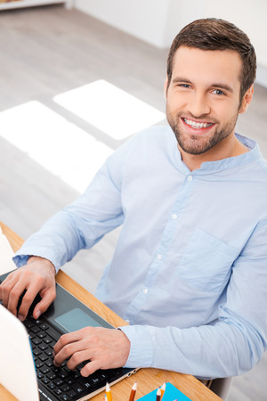 only one man: Taking care of business with smile. Top view of handsome young man in shirt working on laptop and smiling at camera while sitting at his working place