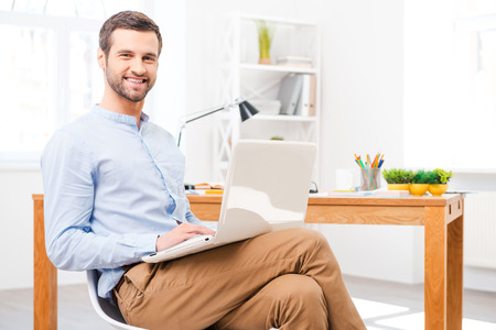 Feeling comfortable in my office. Handsome young man in shirt working on laptop in front of his desk and smiling at camera while sitting at office