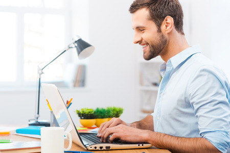 Working with smile. Handsome young man in shirt working on laptop and smiling while sitting at his working place