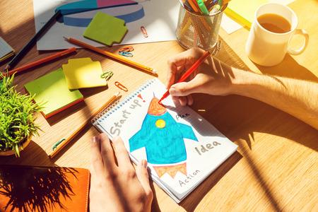 �sketch: S�lo inspirado. Vista superior Primer plano del hombre dibujando en un papel que pone en el escritorio de madera