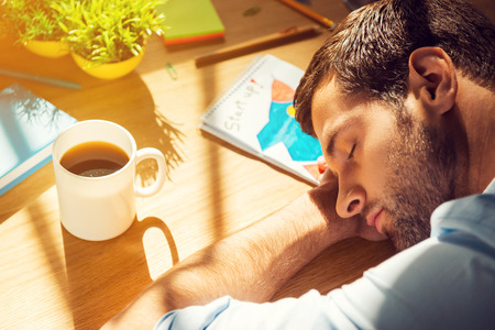 tired eyes: Giving all his energy to work. Close-up top view of tired man sleeping while sitting at his working place Stock Photo