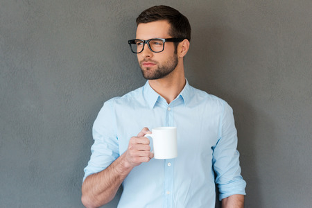 eyewear: Waiting for inspiration. Handsome young man in shirt in eyewear holding cup of coffee and looking way while standing against grey background Stock Photo