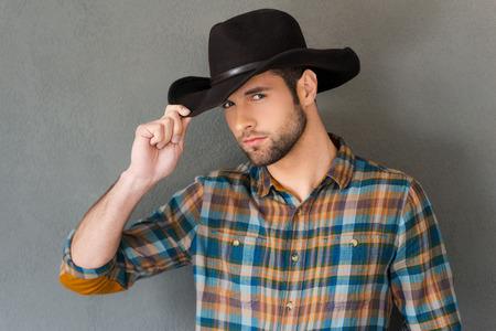 vaquero: Estilo vaquero. Hombre joven hermoso que ajusta su sombrero de vaquero y mirando a la cámara mientras está de pie contra el fondo gris Foto de archivo