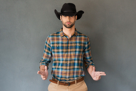 Hands up! Handsome young man wearing cowboy hat and gesturing while standing against grey background