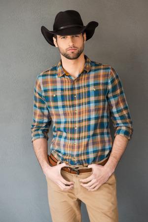 vaquero: Vaquero valiente. Apuesto joven vestido con sombrero de vaquero y mirando a la cámara mientras está de pie contra el fondo gris