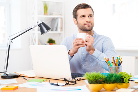 only young adults: A cup of coffee for new ideas. Handsome young man in shirt holding a cup of coffee and looking away while sitting at his working place