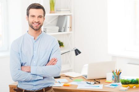 그는 창조적 인 생각을 가지고 있습니다. 잘 생긴 젊은 남자 팔을 넘어 사무실에서 책상에 기대어 동안 카메라를 웃고 팔을 유지 스톡 콘텐츠