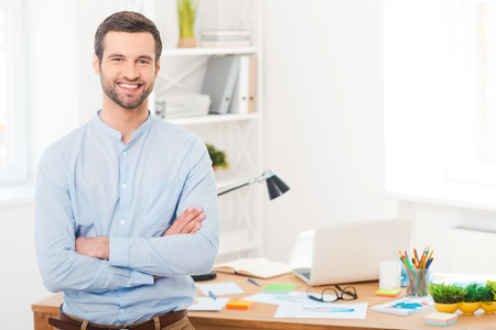 He got creative mind. Handsome young man in shirt keeping arms crossed and smiling at camera while leaning at the desk in office Stockfoto