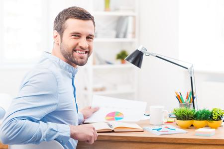 empleado de oficina: Feliz con los resultados de su trabajo. Hombre joven hermoso que sostiene el papel con la carta y sonriendo a la c�mara mientras estaba sentado en su lugar de trabajo