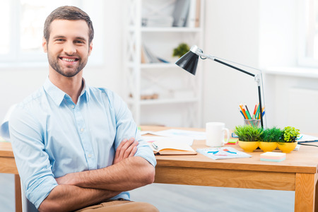 professional man: Time to be productive. Handsome young man in shirt keeping arms crossed and smiling at camera while sitting at his working place