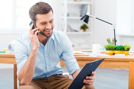 Diskusi o nový projekt. Pohledný mladý muž, mluvil po telefonu a při pohledu na jeho schránky, zatímco sedí na svém pracovním místě Reklamní fotografie