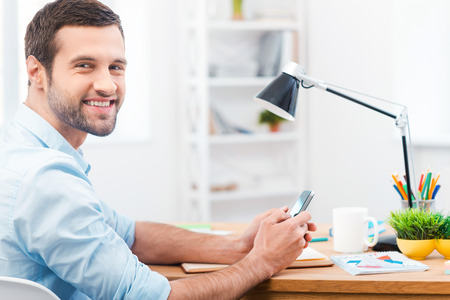 side job: In love with my job. Side view of handsome young man in shirt holding mobile phone and smiling at camera while sitting at his working place Stock Photo
