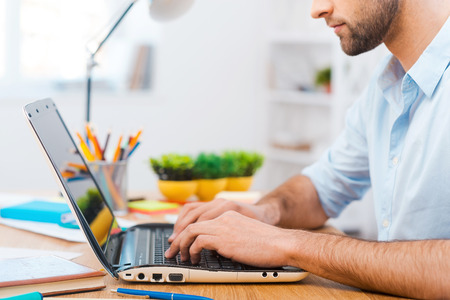 man using computer: Concentrated at work. Cropped image of young man working on laptop while sitting at his working place Stock Photo