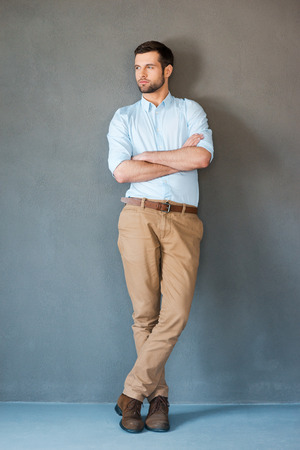 attractive male: Serious and confident. Full length of handsome young man in shirt keeping arms crossed and looking away while standing against grey background Stock Photo
