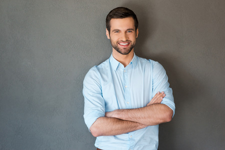 잘 생긴 자신감. 셔츠 유지 팔에 잘 생긴 젊은 남자 건너와 회색 배경에 서있는 동안 카메라에 미소
