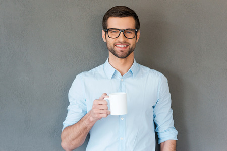 Good coffee for starting your day. Handsome young man in shirt in eyewear holding cup of coffee and smiling at camera while standing against grey background