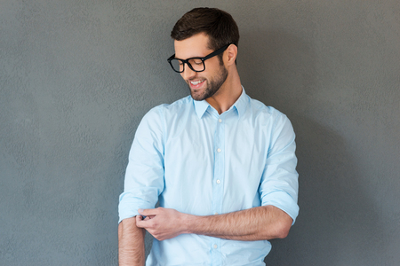 rolledup sleeves: Preparing to work hard. Handsome young man in shirt adjusting sleeves and smiling while standing against grey background Stock Photo