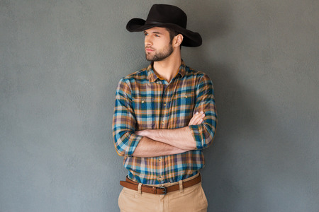 Serious and confident cowboy. Handsome young man in cowboy hat keeping arms crossed and looking away while standing against grey background Zdjęcie Seryjne
