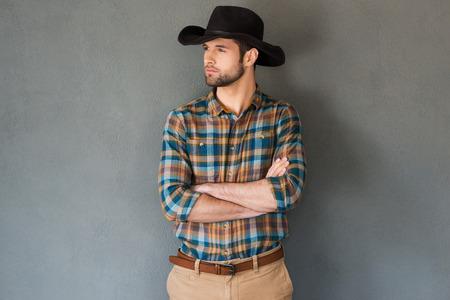 vaquero: Vaquero serio y confiado. Apuesto joven en el sombrero de vaquero mantener los brazos cruzados y mirando a otro lado mientras est� de pie contra el fondo gris Foto de archivo