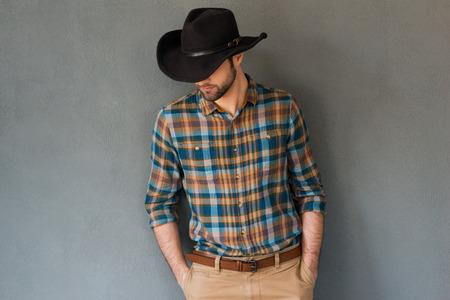 vaquero: Costura del vaquero. Retrato de hombre joven con sombrero de vaquero y mirando hacia abajo mientras est� de pie contra el fondo gris Foto de archivo
