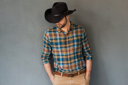 Cowboy couture. Portrait of young man wearing cowboy hat and looking down while standing against grey background
