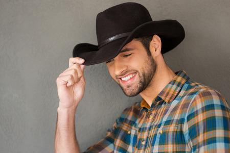 vaquero: Sonriente vaquero. Hombre joven hermoso que ajusta su sombrero de vaquero y sonriente mientras está de pie contra el fondo gris