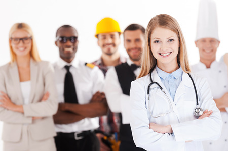 When I grow up I will be a doctor. Beautiful young female doctor keeping arms crossed and smiling while group of people in different professions standing in the background photo