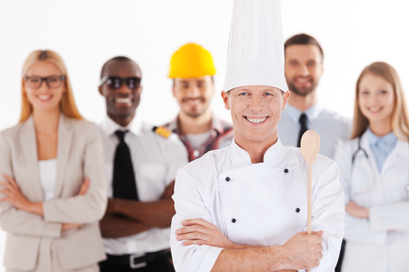 When I grow up I will be a chef. Confident male chef in uniform keeping arms crossed and smiling while group of people in different professions standing in the background photo